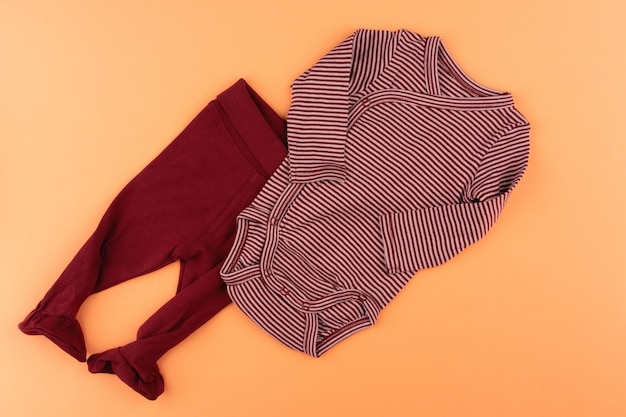 Kleidung des kleinen mädchens auf orange oberfläche
