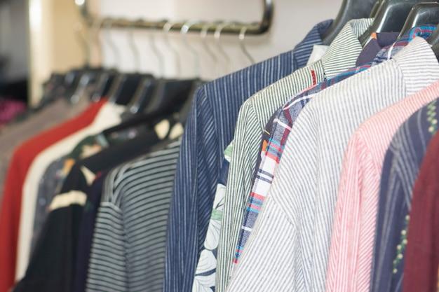 Kleidung, die an den aufhängern im shopspeicher hängt