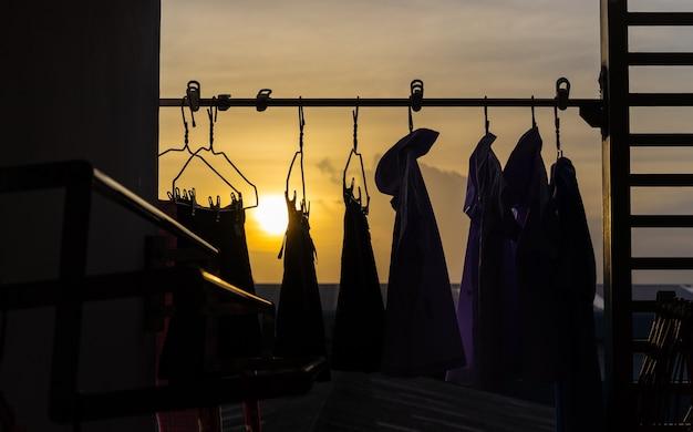 Kleidung, die an der wäscheleine mit sonnenuntergang hängt