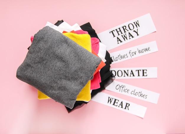 Kleidung, die im kleiderschrank für spenden sortiert, im büro und zu hause getragen und mit papiernotizen auf weichem rosa hintergrund entsorgt wird.