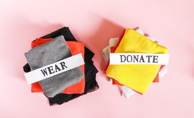 Kleidung, die in der hausgarderobe zur spende sortiert und mit papiernotizen auf weichem rosa hintergrund getragen wird.