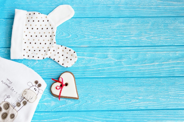 Kleidung für neugeborenes und lebkuchenherz auf einer blauen holzwand