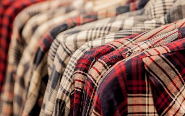 Kleidung hängt an einem regal. kleiderbügel mit hemden.