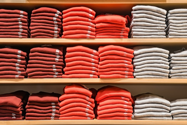 Kleidung im laden angezeigt. viele warme pullover in leuchtenden farben sind ordentlich in einer reihe auf den ladenregalen gestapelt. stapel von mehrfarbiger gestrickter wollkleidung. t-shirt im regal.