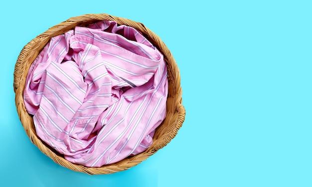 Kleidung im wäschekorb auf blauem hintergrund. speicherplatz kopieren