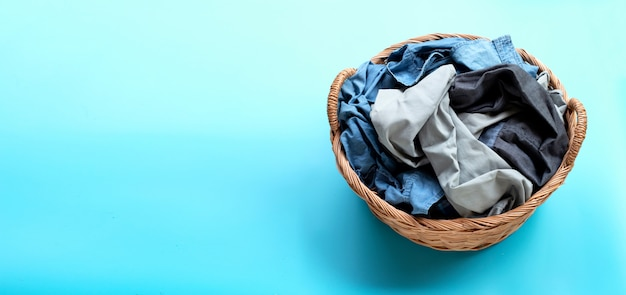 Kleidung im wäschekorb auf blauem hintergrund.