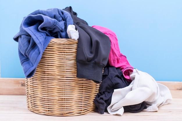 Kleidung in einem hölzernen korb der wäscherei auf hölzerner tabelle im raum