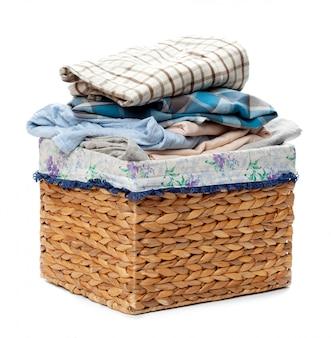 Kleidung in einem hölzernen korb der wäscherei lokalisiert auf weißem hintergrund