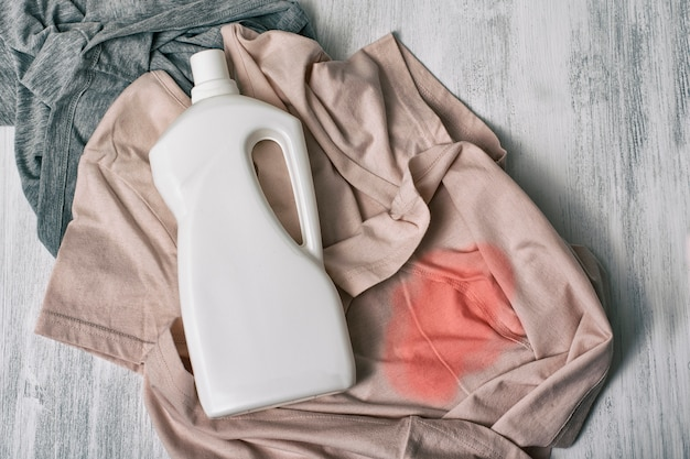 Kleidung mit flecken und einer flasche reinigungsmittel. ansicht von oben