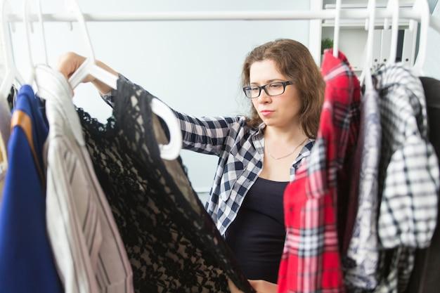 Kleidung, mode, menschenkonzept - ernsthafte junge frau, die kleidung in ihrem kleiderschrank wählt