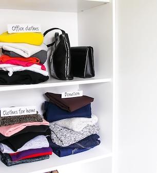 Kleidung und accessoires, die in der hauptgarderobe auf weißem regalhintergrund sortieren. bürokleidung, kleidung für zu hause, spendenzettel.