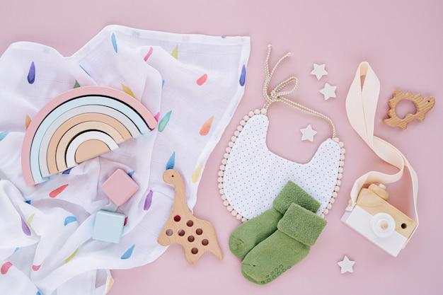 Kleidung und accessoires für neugeborene. spielzeug, lätzchen und socken mit musselin-wickeldecke auf rosa hintergrund. baby-dusche-konzept. flache lage, ansicht von oben