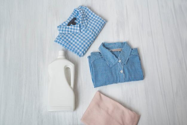 Kleidung und flasche mit waschmittel. ansicht von oben