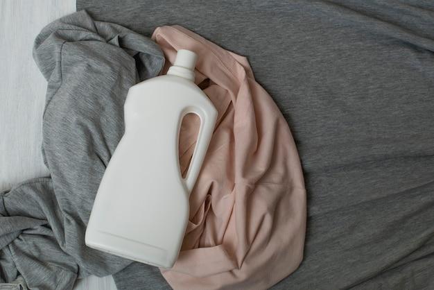 Kleidung und flasche mit waschmittel. draufsicht