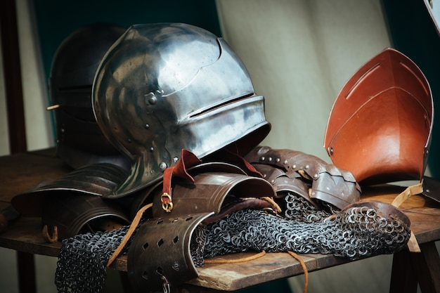 Kleidung und werkzeuge eines mittelalterlichen ritters auf dem tisch