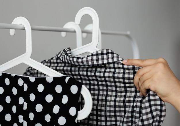 Kleidung wird vom verkaufseinkauf auf ein gestell gehängt