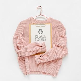Kleidungskonzept recyceln. blassrosa strickpullover mit zwischenablage auf weißem hintergrund. herbst- und winterkleidung.