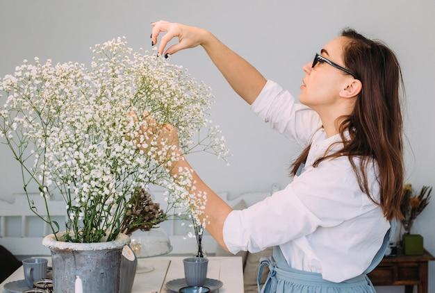 Kleinbetrieb. florist mädchen ist in einem blumenladen konzentriert. helles studio des blumenmusters, dekor. blumenlieferung, auftragserstellung