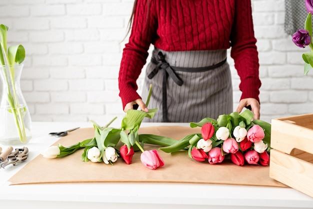 Kleinbetrieb. frauenflorist, der einen blumenstrauß von frischen bunten tulpen macht Premium Fotos