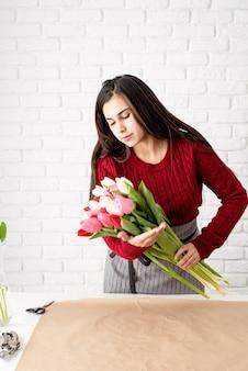 Kleinbetrieb. frauenflorist, der einen blumenstrauß von frischen bunten tulpen macht