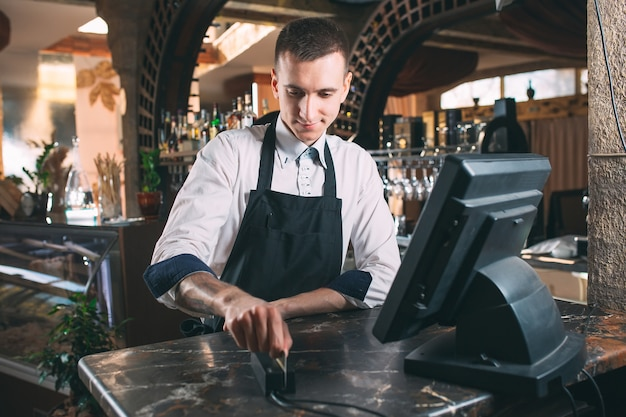 Kleinbetrieb-, leute- und servicekonzept - glücklicher mann oder kellner im schutzblech am zähler mit der geldkassette, die an der bar oder an der kaffeestube arbeitet