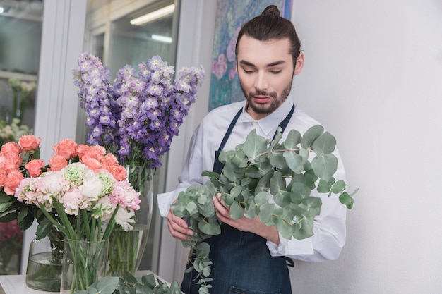 Kleinbetrieb. männlicher florist im blumenladen. dekorationen und arrangements machen