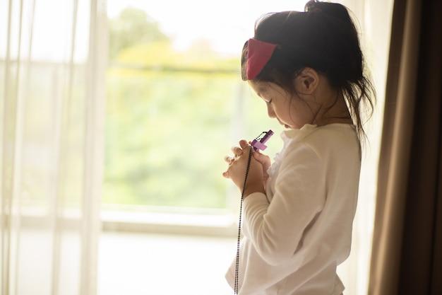 Kleine asiatin, die mit holzkreuz betet