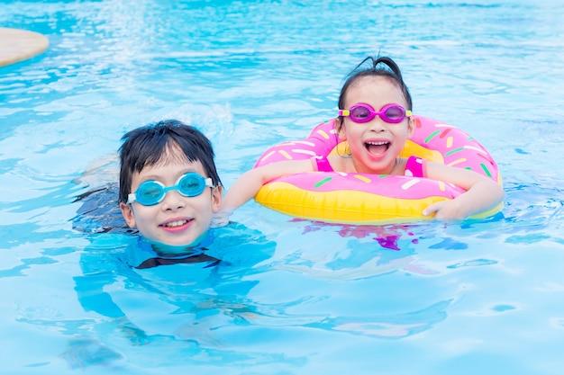 Kleine asiatische geschwister glücklich zusammen im swimmingpool