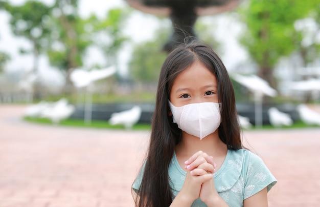 Kleine asiatische junge mädchen tragen eine gesichtsmaske und beten geste, um covid-19 während des ausbruchs des coronavirus in thailand zu stoppen