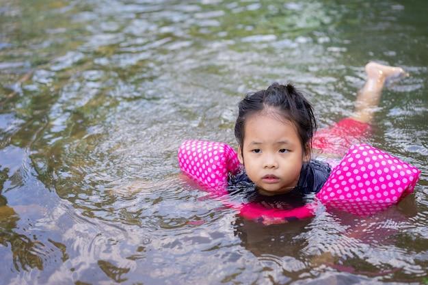 Kleine asiatische mädchen schwimmen im fluss
