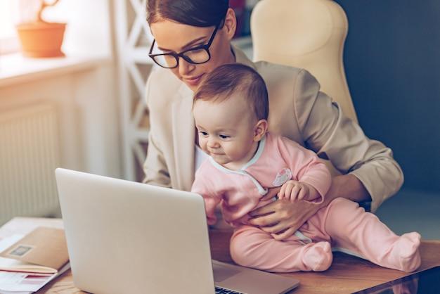 Kleine assistentin. kleines mädchen mit laptop beim sitzen auf dem schreibtisch mit ihrer mutter im büro