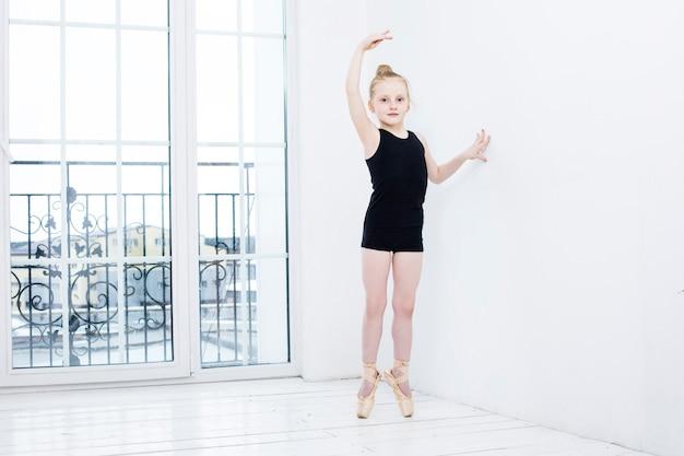 Kleine baby-balletttänzerin, die sich im hellen raum auf glücklich und niedlich ausdehnt