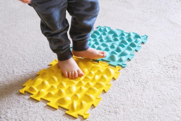 Kleine babyfüße auf dem gerippten teppich.