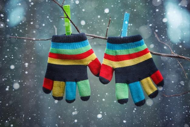Kleine babyhandschuhe / -handschuhe, die durch einen thread am wintertag unter dem fallenden schnee hängen.