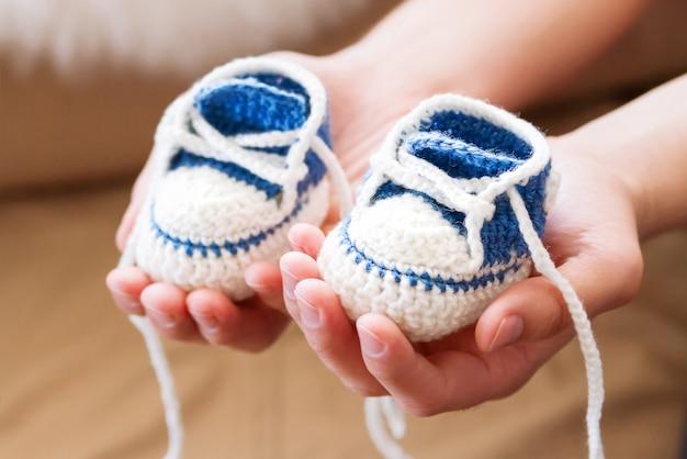 Kleine babyschuhe. handgestrickte erste turnschuhe für jungen oder mädchen. häkeln sie handgemachte stiefeletten in papas händen. neu vater präsentiert gestrickte schuhe.