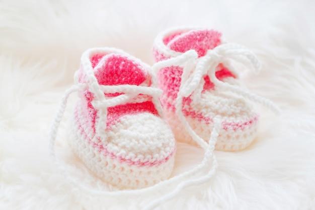 Kleine babyschuhe. handgestrickte erste turnschuhe für neugeborene. häkeln sie handgemachte rosa stiefeletten