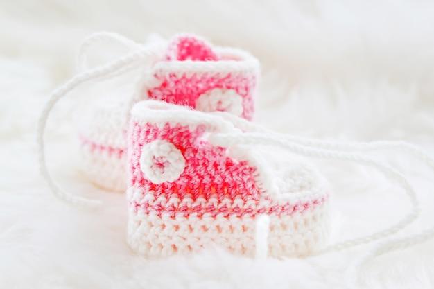 Kleine babyschuhe. handgestrickte erste turnschuhe für neugeborene. häkeln sie handgemachte stiefeletten