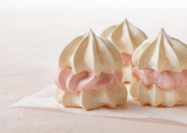 Kleine baiserkuchen aus eiweißkeksen und erdbeercreme auf rosa hintergrund