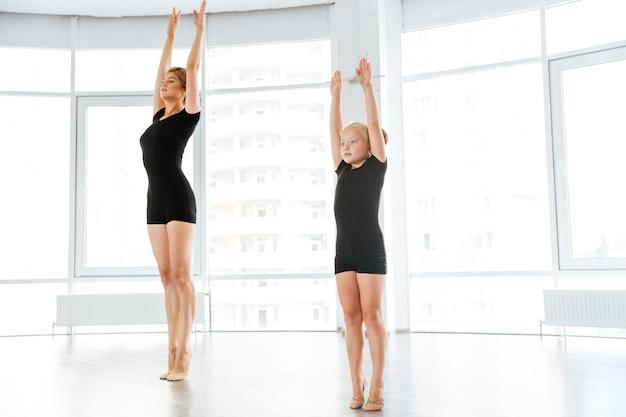 Kleine ballerina, die klasse mit persönlichem ballettlehrer im tanzstudio hat