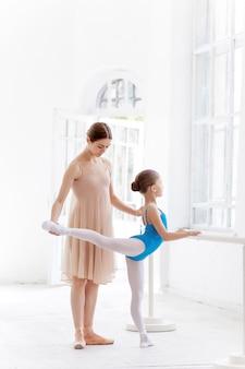 Kleine ballerina, die mit persönlichem lehrer im tanzstudio aufwirft