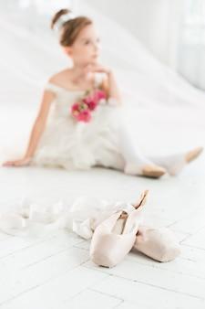 Kleine ballerina in weißem tutu im unterricht an der ballettschule