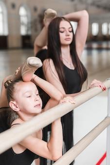 Kleine ballerina mit ballettlehrer, der am ballett barre aufwirft