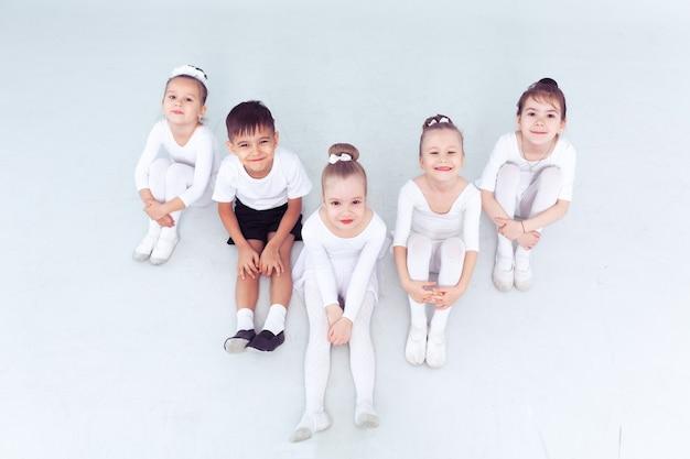 Kleine ballerinas mädchen und junge machen spagat auf weißem boden kopie raum