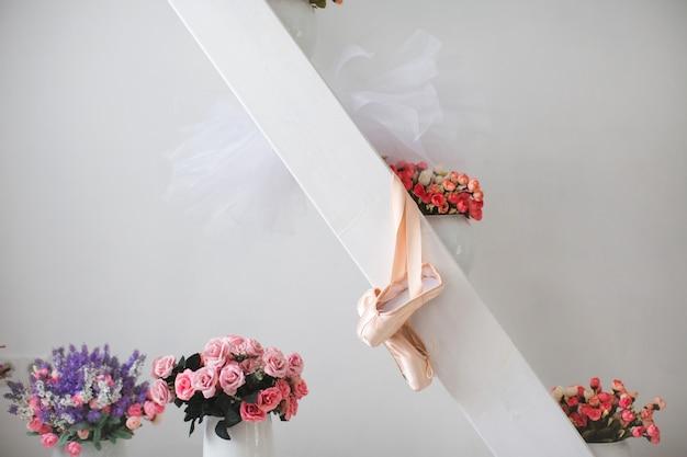Kleine ballett-spitzenschuhe vor dem hintergrund der blumen