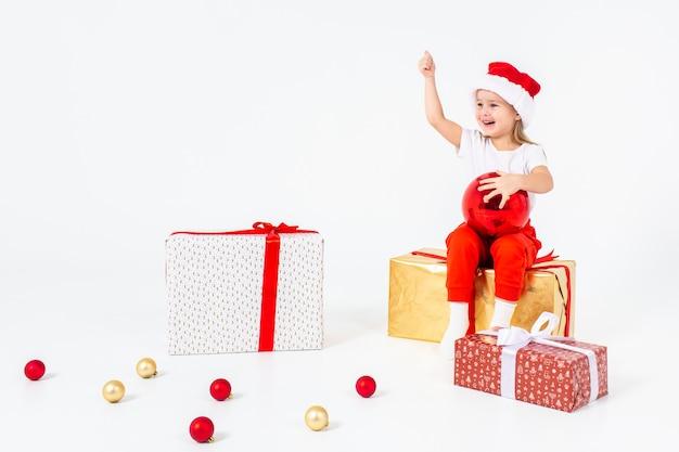 Kleine blonde kinder in sankt-hut, der auf geschenkboxen sitzt und daumen hochhält. isoliert auf weißem hintergrund feiertage, weihnachten, neues jahr, weihnachtskonzept. exemplar.