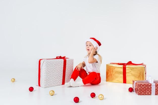 Kleine blonde kinder in sankt-hut, der zwischen geschenkboxen sitzt und ihre backe hält