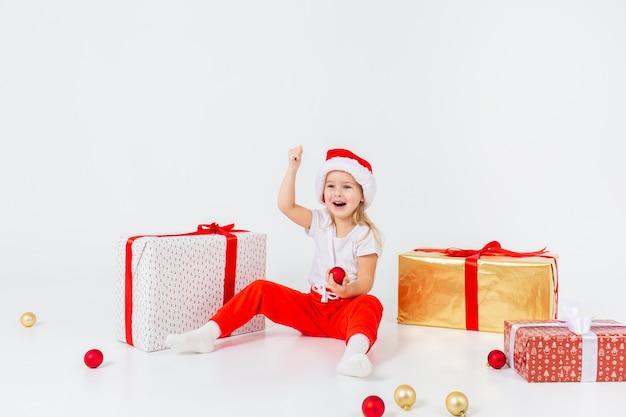Kleine blonde kinder in sankt-hut, der zwischen geschenkboxen sitzt und mit weihnachtsbällen spielt