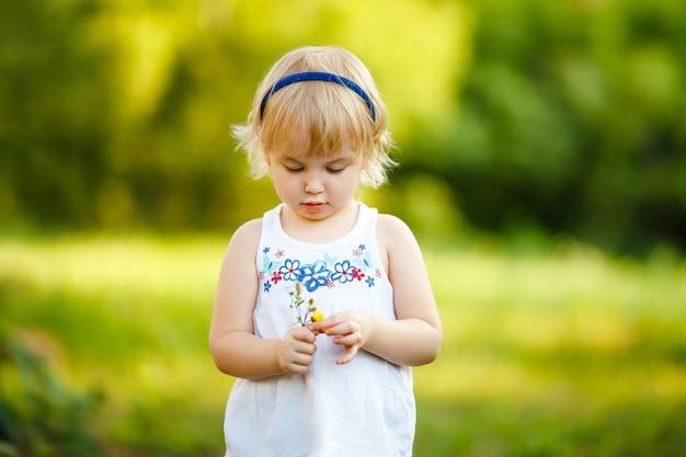 Kleine blondine 2-3 jahre altes mädchen, das im sommerpark spielt und blumen riecht. kinderaktivitätskonzept