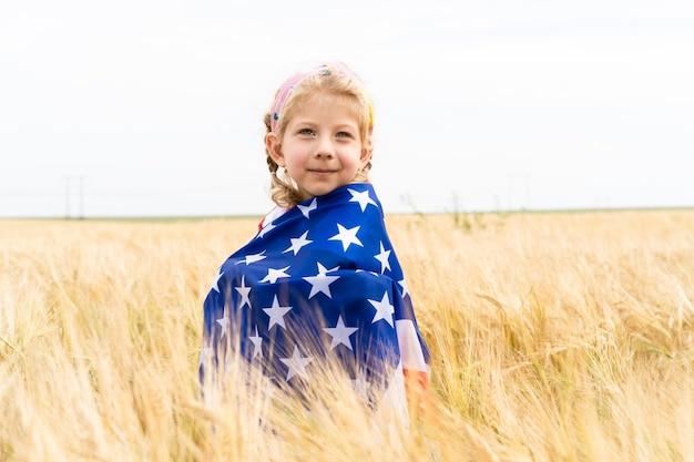 Kleine blondine in einem roggenfeld mit einer amerikanischen flagge, usa independence day.