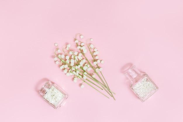 Kleine blüten von maiglöckchen und glasflasche mit trockenen blütenblättern